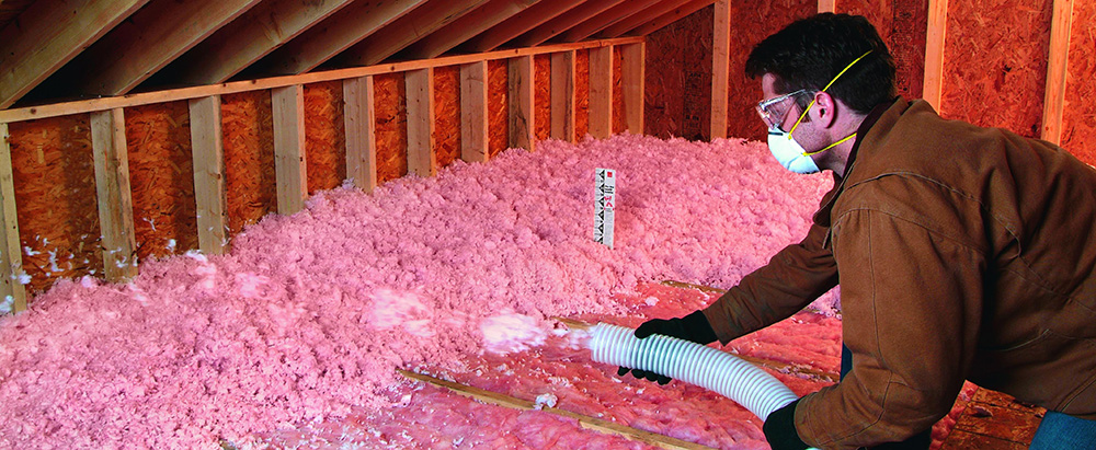 A man blowing insulation.